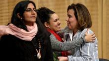 Seattle City Councilwoman Kshama Sawant, left, as fellow Councilwoman Debora Juarez, right, is embraced by Rachel Heaton, a Muckleshoot tribal member, before Wednesday's council meeting. (Elaine Thompson / AP)