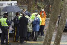SFU molecular biology department chair Lynne Quarmby waving to supporters in handcuffs during her arrest on Burnaby Mountain on Friday.