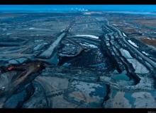(A land of pits, fumes, and poisoned pools as far as the eye can see. Canada, in its mad quest for oil, has turned a pristine boreal forest into a place that is a stunning likeness to Tolkien's Mordor. Image source: Garth Lenz's TED Talk.)