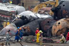 Firemen use foam to hose down a railcar as cleanup crews remove one of the toppled rail cars in Lac-Mégantic on Friday July 19, 2013.  Photograph by: Allen McInnis/Montreal Gazette , Postmedia News