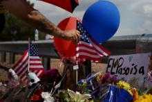 On Aug. 4, 2019, a man places an American flag on a makeshift memorial outside the Walmart store in El Paso, Texas, where a mass shooting occurred the previous day.