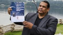 Rueben George holds a copy of Tsleil-Waututh's assessment of the Trans Mountain Pipeline project. Photo: Carlos Tello