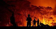 Residents look on as flames burn through bush on January 4, 2020 in Lake Tabourie, Australia. (Photo: Brett Hemmings/Getty Images)
