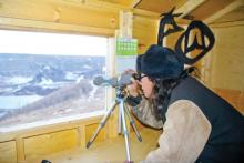 George Desjarlais looks through a telescope at the Site C dam construction from an observation shack built by the Treaty 8 Tribal Association overlooking the Peace River.   Photo By William Stodalka - See more at: http://www.alaskahighwaynews.ca/regional-news/site-c/site-c-opponents-keeping-an-eye-on-dam-s-construction-from-new-observation-shack-1.2111836#sthash.BdkmakXe.3OEmiFp9.dpuf