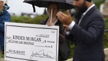 NDP Leader Jagmeet Singh speaks as a woman holds a novelty cheque made out to Kinder Morgan at a rally against the proposed Trans Mountain pipeline project, on Parliament Hill in Ottawa on Tuesday, May 22, 2018. THE CANADIAN PRESS/Justin Tang