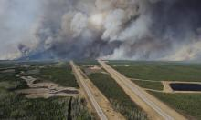 Smoke from fires billows south of Fort McMurray as seen from a helicopter over Highway 63. Photograph: Mcpl Vanputten/AFP/Getty Images
