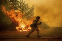 A firefighter races to save a home in Lakeport, Calif. The residence eventually burned. (Noah Berger / AP)