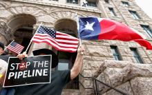 Texan Eddy Radillo holds a Texas flag and a sign opposing the Keystone XL pipeline during a rally in Paris, Texas in 2012.Sam Craft/The Paris News, via AP