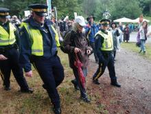 Jean Swanson is accompanied by police during her arrest at the Kinder Morgan terminal in Burnaby. Photo by Riaz Behra.