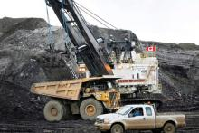 A pickup truck is seen passing a mining shovel at an oil sands mine near Fort McMurray, Alta., in a file photo.  JEFF MCINTOSH/THE CANADIAN PRESS