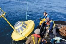 A crew handles a buoy that measures wave energy. Bryson Robertson, UVic adjunct professor of mechanical engineering, said reduced costs alone make wave energy worth examining for Hesquiaht First Nation, since diesel generators are expensive.   Photograph By University of Victoria